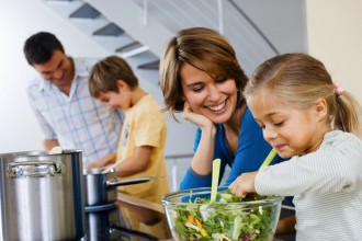 Parents cooking with their children in kitchen --- Image by © beyond/Corbis